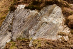 Rock strata. Colourful layered rock eroded by centuries of weather and climatic conditions found here in the countryside of Scotland, Gt. Britain