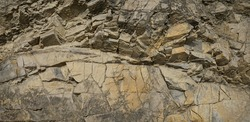 Rock texture. Stone background. Old weathered crumbling mountain surface in cracks background. Light brown rock background.