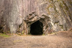 Rock wall with a dark hole, entrance to the cave in Spro, Mineral historic mine. Nesodden Norway. Nesoddtangen peninsula.