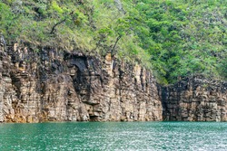 Rock walls of on the shore of the Lake of Furnas, Capitólio MG, Brazil. Green water of the lake, sedimentary rocks and the vegetation growing up the rocks.