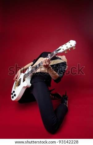 rock woman in black leather on red play guitar