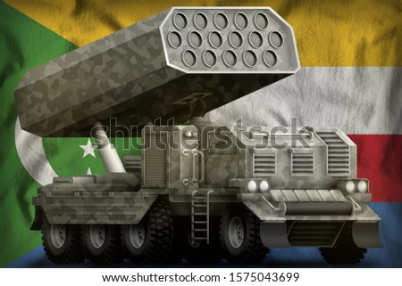 rocket artillery, missile launcher with grey camouflage on the Comoros flag background. 3d Illustration