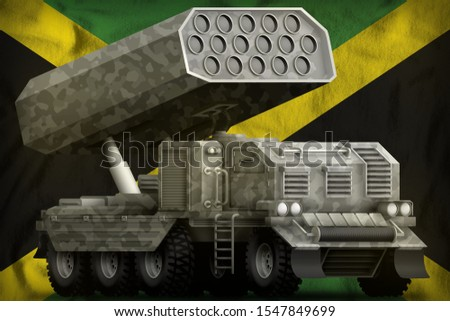 rocket artillery, missile launcher with grey camouflage on the Jamaica flag background. 3d Illustration