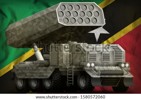 rocket artillery, missile launcher with grey camouflage on the Saint Kitts and Nevis flag background. 3d Illustration