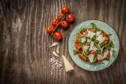 Rocket salad with cherry tomato and pecorino in plate on wooden tacbe, top view and copy space