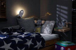 Rocket shaped night lamp on wall in child's room