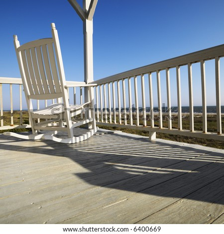 Rocking chair on porch with railing overlooking beach at Bald Head Island, North Carolina.