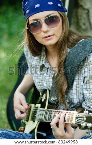 Rocking girl on a nature with guitar