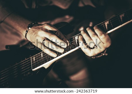 Rockman Playing Electric Guitar Closeup Photography. Hands on Guitar. Elegant Browny Color Grading.