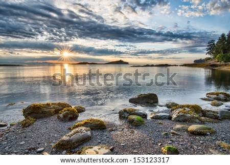 Rocks along coast with sun star #153123317