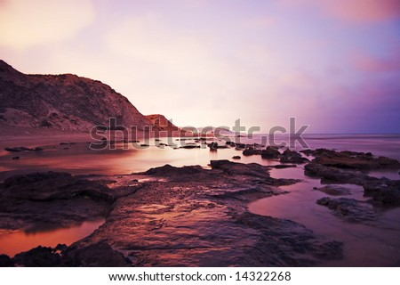 rocks and ocean long exposure sunset warm tones - stock photo
