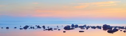Rocks at the coast of Kasmu (captain's village) at sunset. Estonia, Baltic sea. Clear blue sky, pink clouds. Panoramic view. Travel destinations, vacations, eco tourism