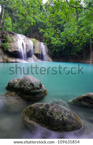 Rocks in Blue Lake with Flowing Water at Erawan Waterfall in Thailand - stock photo