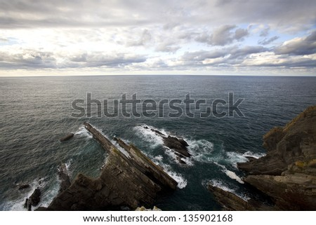 Rocks in Cantabric Sea coast. Sea coast panoramic with rocks at foreground. Asturias, North Spain