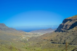 Rocks in the north of the Gran Canaria island. The road passes over the cliffs, the ocean is visible