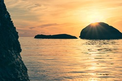 Rocks in the sea at colorful sunrise. The sunbeams of the rising sun sparkle from behind the rock