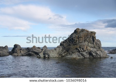 Rocks in the sea near the shore. The water is calm, Sunny weather, blue sky, clouds. Nature is the best sport Sakhalin, Russia.