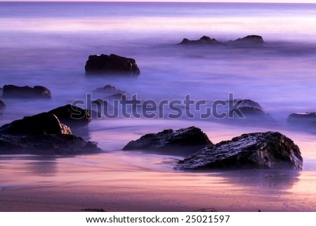 Rocks in the surf at sunset along the California coast near Malibu.  The colors of dusk reflect in the mists and water surrounding the jet black stones