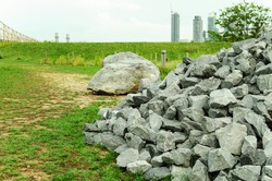 Rocks, material for building parks and city reconstraction. Green grass and city view