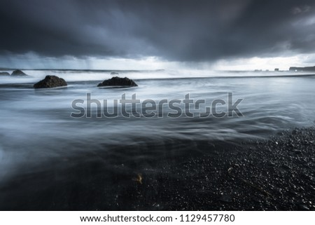Rocks on a black sand beach in Iceland with reflection in the Sea and a dark sky in misty moody weather with dark colors and a rough sea in landscape format with a storm approaching