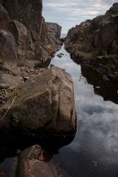 Rocks on stream flowing into Lake Superior, granite cracks, calm