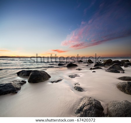 rocks on the beach with red clouds on square format