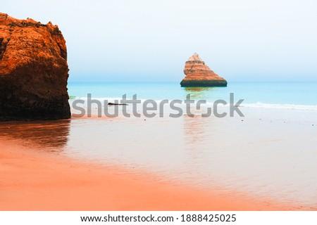 Rocks on the shore of Atlantic ocean in Algarve, Portugal. Beautiful seascape in misty morning