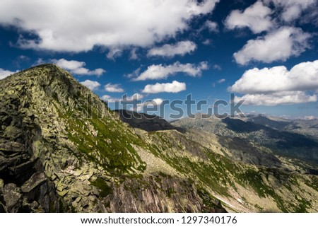 Rocks under blue sky with clouds. View of mountain valley. Tourism, travel to mountains. #1297340176
