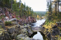 Rocku coast of river covered by autumn forest