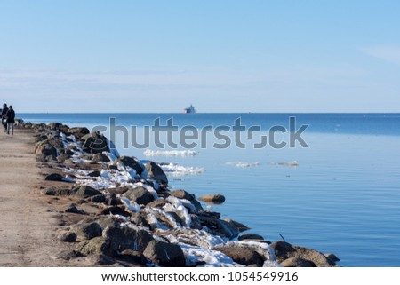 Rocky and snowy breakwater and a ship closing in to a port.