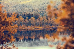 Rocky bank of mountain lake in misty autumn morning. Beautiful autumn nature of Norway. Reflection on the lake