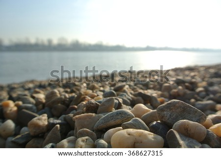 Rocky beach and a frozen lake #368627315