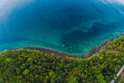Rocky beach idyllic sea island with green tree forest aerial view