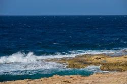 Rocky beach in St Paul's Bay, Malta. Beautiful stormy blue mediterranean sea.  Selective focus.