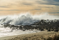 Rocky beach sunset and stormy ocean waves splashing high into the air against rocks at Morro Bay, Central California Coast