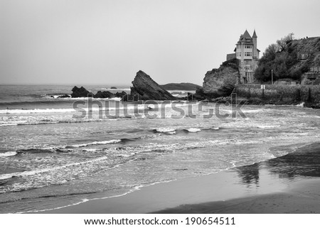 Rocky black and white, coastal beach seascape in Biarrtiz, France on the Atlantic ocean. Surfers in the water surfing waves towards a sandy beach. / Seascape in Biarrtiz, France.
