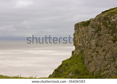 Rocky cliff by a stormy sea - stock photo