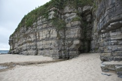 Rocky cliff face with a cave, filled with sand on tropical cliff face and grass, sea side ocean