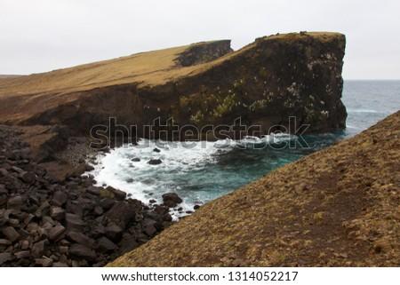 Rocky cliff with grass on Iceland Reykjanes peninsula volcanic stones shore coast line landscape