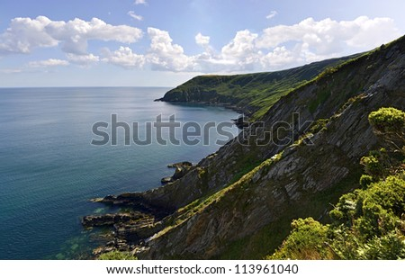 Rocky cliffs covered in grass with sea on a sunny day