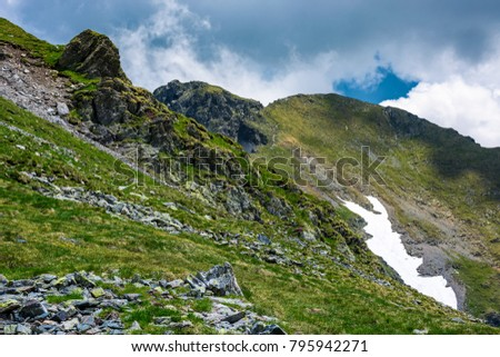 rocky cliffs on grassy slopes with snow in summer. lovely nature scenery under the cloudy sky in Fagaras mountains, Romania #795942271