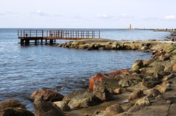 Rocky coast at promenade and pier in Mangalsala ending with red lighthouse, located at Riga sea port, Latvia, Europe