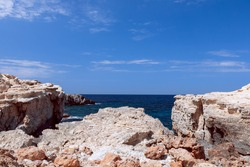 Rocky coast by the bay Cala Portinatx. Ibiza. Balearic Islands, Spain