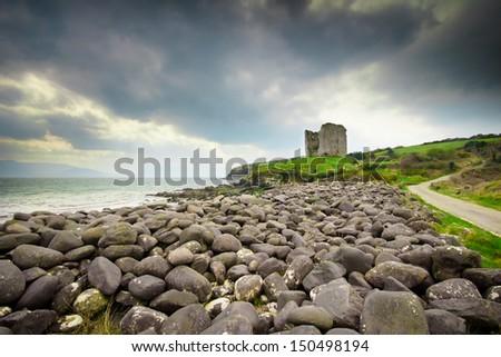 Rocky coast leading up to castle ruins along the Dingle coast in Ireland