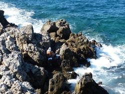 Rocky coast Mediterranean sea, Rethymno Crete, Greece,  local male greek fisherman catches fish in stormy waves, Summer fishing, scenic coastal rocks, stony beach.
