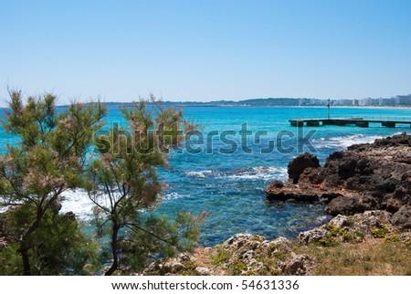 Rocky coast of Cala Bona and sunlit Mediterranean Sea under solid blue sky, Majorca island, Spain