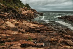 Rocky coast of the Atlantic Ocean. Gloomy weather. Acadia National Park. USA. Maine. Dramatic seascape.