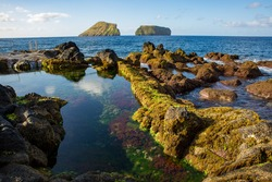 Rocky coast of the sea. Natural pools of Terceira, part of the archipelago of the Azores, with the Ilhéus das Cabras in the background.