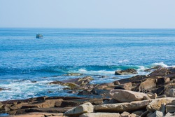 rocky coast on the Atlantic ocean at Cape Ann, Massachusetts with a fishing boat in the distance