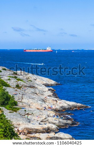 Rocky coast with sunbathing people and a cargo ship on the sea #1106040425